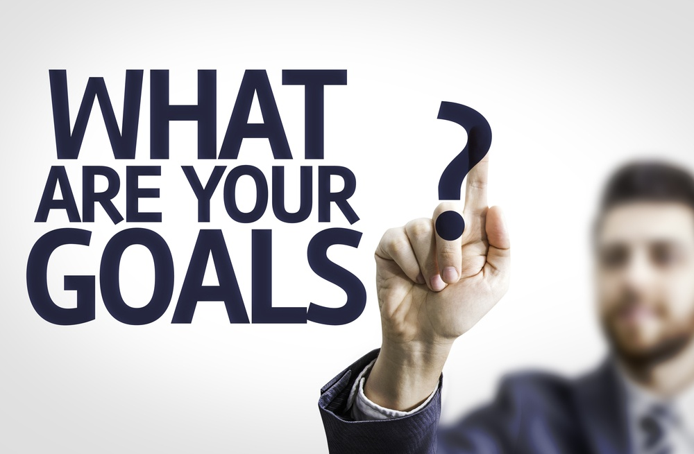 Business man pointing to transparent board with text What are Your Goals?.jpeg
