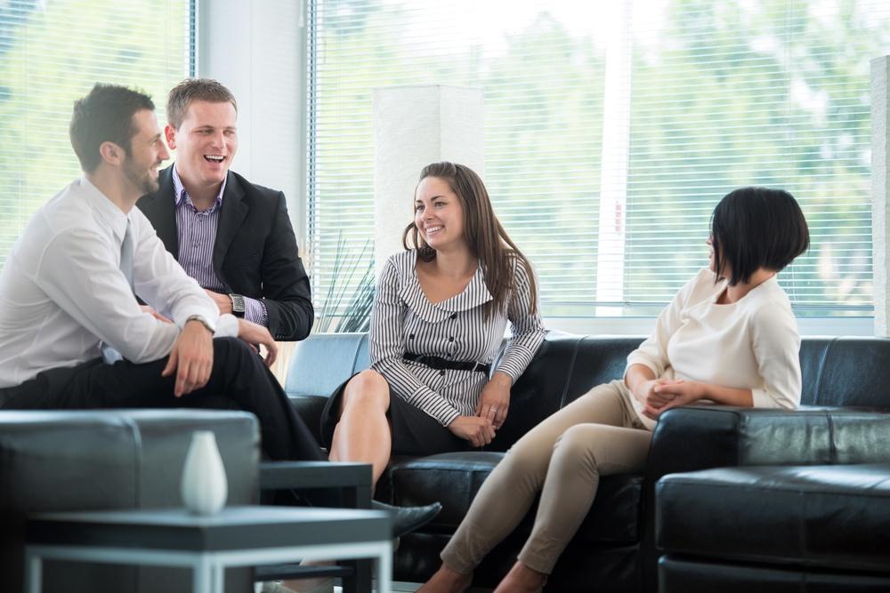 Four business people talking on a break in modern environment.jpeg
