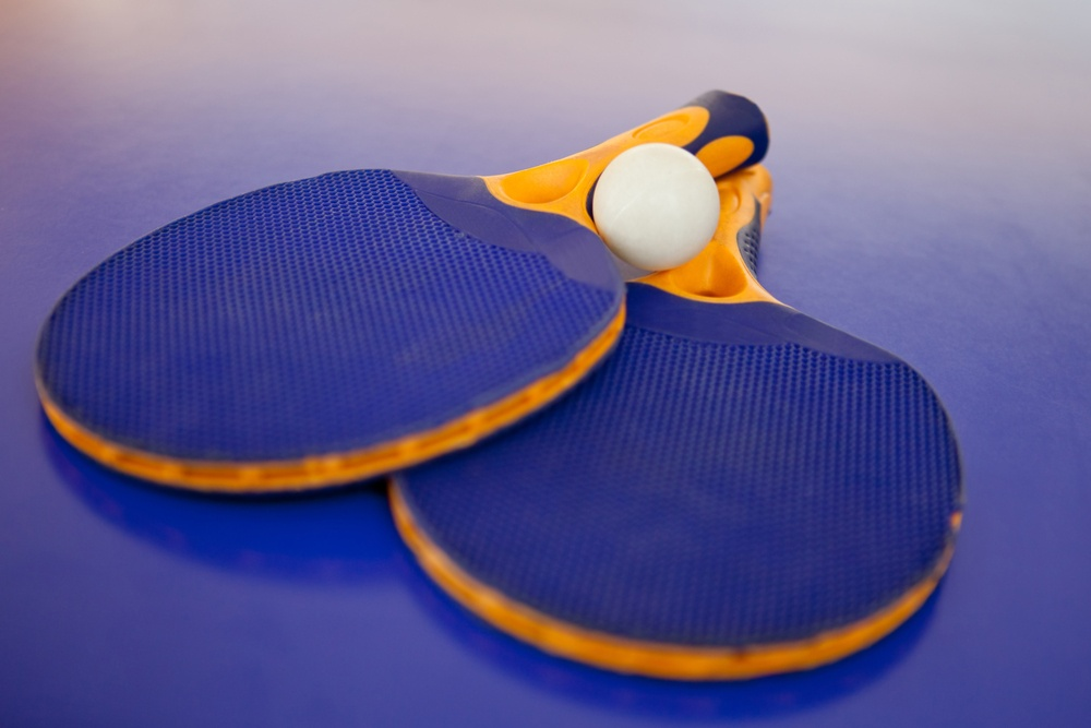Ping pong set with two blue rackets and a white ball.jpeg