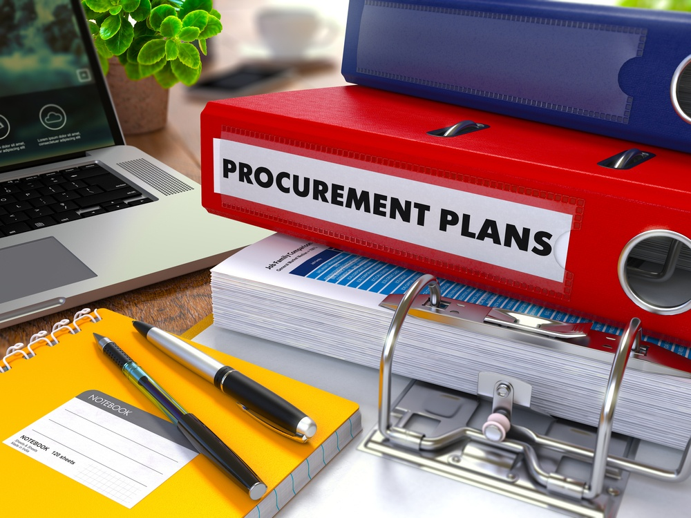 Red Ring Binder with Inscription Procurement Plans on Background of Working Table with Office Supplies, Laptop, Reports. Toned Illustration. Business Concept on Blurred Background.