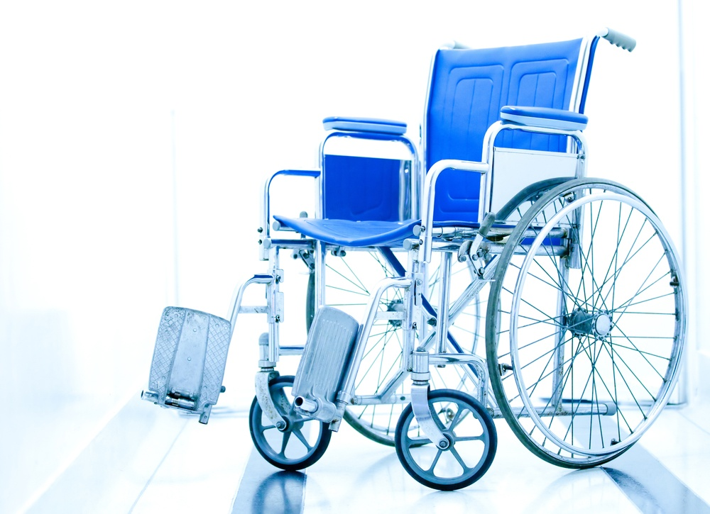 Wheelchair at the entrance of a hospital over a white background.jpeg