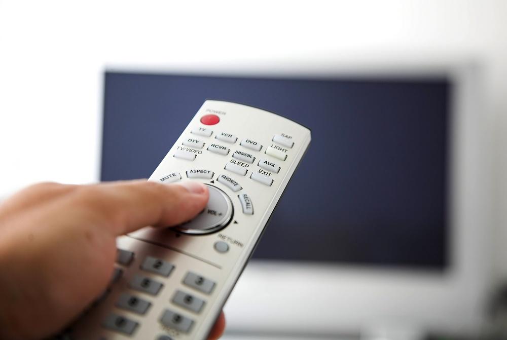 tv remote control with big flatscreen at the back.jpeg
